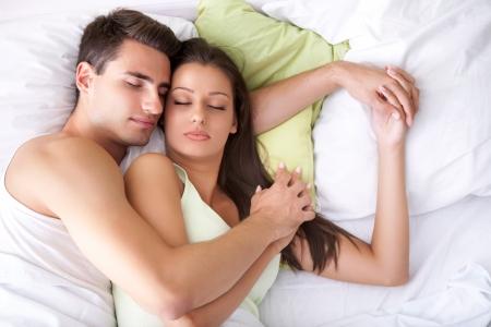 Foto de  Embracing young couple sleeping on the bed - Imagen libre de derechos