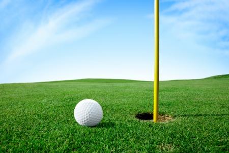 Golf ball on green grass next hole