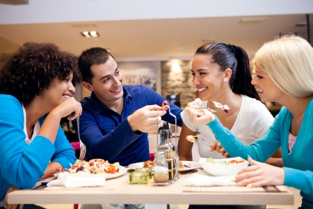 Photo for  Happy teenagers having fun while lunch at restaurant  - Royalty Free Image
