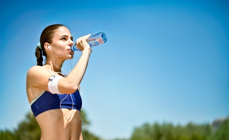 Foto für woman athlete takes a break,  she drinking water, out on a run on a hot day - Lizenzfreies Bild