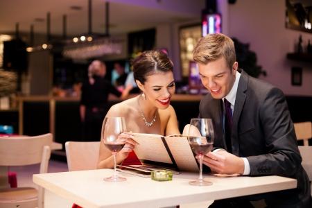 Photo pour Couple reading  at menu together in a restaurant - image libre de droit