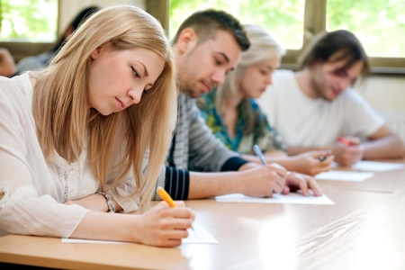 Foto de  group of students takes the test in class - Imagen libre de derechos