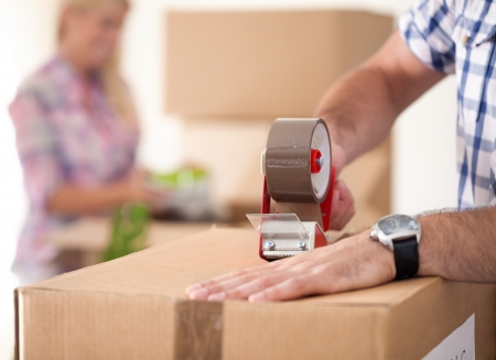 Foto de  Close up of male hand packing cardboard box, concept moving house - Imagen libre de derechos