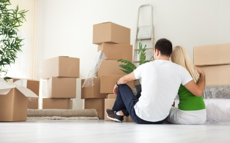 Photo pour  Couple sitting  and looking  lot of moving boxes, back view - image libre de droit