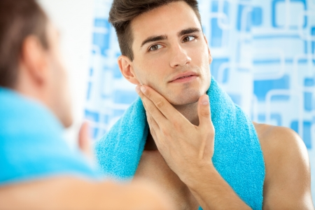 Photo pour  Young handsome man touching his smooth face after shaving - image libre de droit