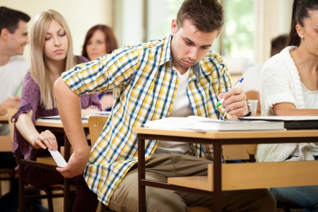 Foto de  Students during test cheating with cheat sheet - Imagen libre de derechos