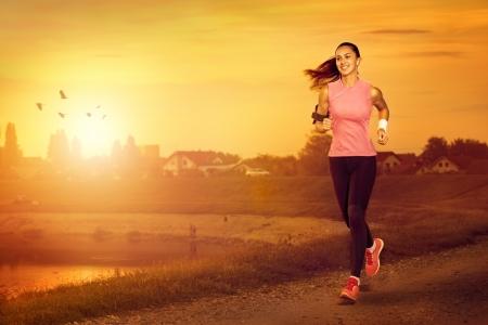 Photo pour Young attractive woman jogging outdoor on sunset - image libre de droit