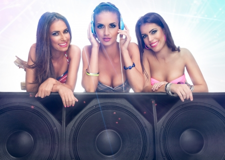 Photo for Three cute girls listening music on large speaker - Royalty Free Image