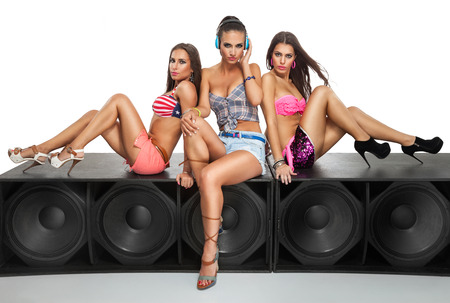 Photo for Sexy girls friends sitting on large speaker - Royalty Free Image