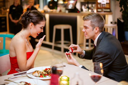 Photo pour  Young man romantically proposing to girlfriend and offering engagement ring - image libre de droit