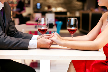 Photo pour Couple in love holding hands together on table in restaurant, close up - image libre de droit