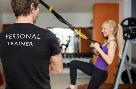 Foto de  Personal trainer, with his back facing the camera, looking at his client - Imagen libre de derechos