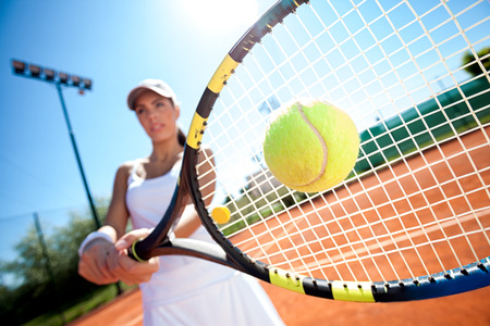 Foto per young woman playing tennis on a sunny day - Immagine Royalty Free