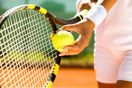 Photo pour  Player's hand with tennis ball preparing to serve - image libre de droit