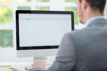 Foto de Business man sitting front of empty monitor, back view - Imagen libre de derechos