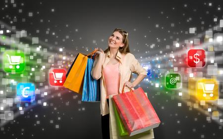Foto de happy shopping woman surrounded by glow icons of e-commerce - Imagen libre de derechos