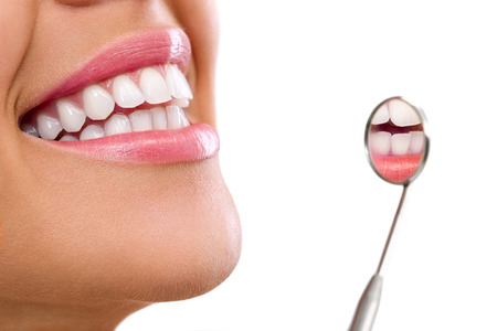 Photo pour  Healthy woman teeth and a dentist mouth mirror  - image libre de droit