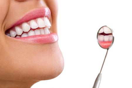 Foto de  Healthy woman teeth and a dentist mouth mirror  - Imagen libre de derechos