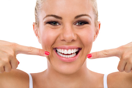Photo for  Smiling woman pointing in her perfect teeth , isolated over white  - Royalty Free Image