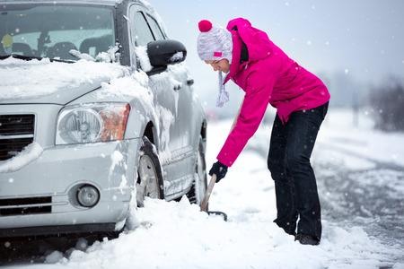Foto de woman shoveling and removing snow from her car, stuck in snow - Imagen libre de derechos