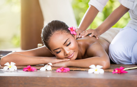 Foto de Smiling woman enjoying a massage, back massage - Imagen libre de derechos