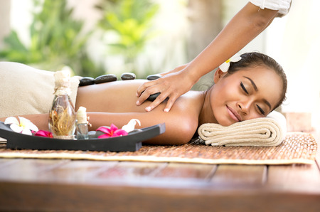 Photo for Stone massage, beautiful woman getting spa hot stones massage in spa salon - Royalty Free Image