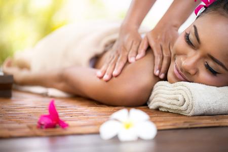 Photo pour Beautiful young woman at spa outdoor, stone massage - image libre de droit