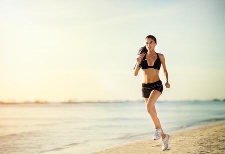 Photo pour Running woman running on seaside. woman fitness sunrise/sunset jogging workout wellness concept. - image libre de droit