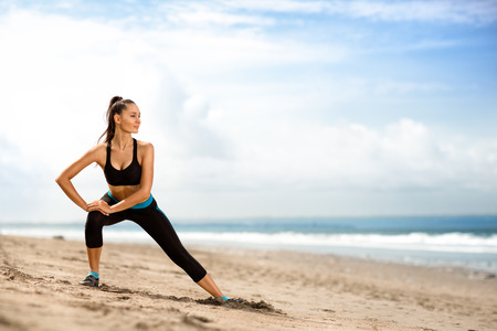 Photo for young beautiful sportswoman doing exercises on beach - Royalty Free Image