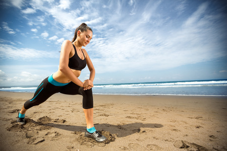 Photo for Attractive woman stretching legs after run on beach - Royalty Free Image