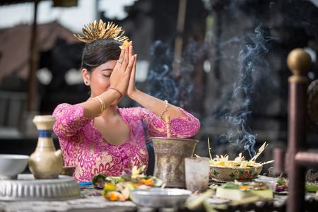 Photo for Beautiful Asian woman prays in the temple. Bali. Indonesia - Royalty Free Image