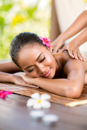 Photo for young woman having massage outside in tropical garden - Royalty Free Image