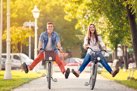 Photo for Happy funny young couple riding on bicycle - Royalty Free Image
