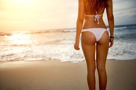 Sexy back of a beautiful woman in bikini on sea background. Sexy buttocks