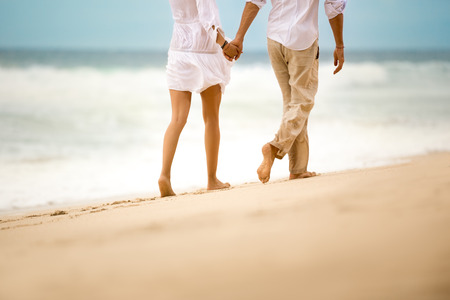 Photo for Barefoot couple walking on sandy beach - Royalty Free Image