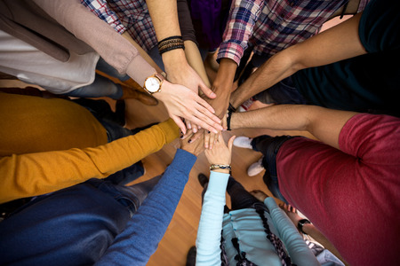 Foto de Unit and concord in multiethnic team, all hands together - Imagen libre de derechos
