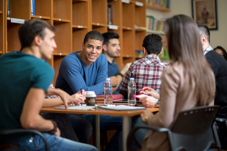 Photo for Young Latino American student socialize with friends after class in library - Royalty Free Image