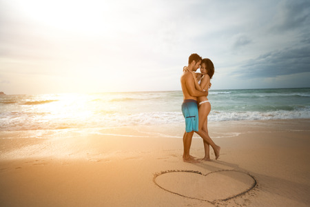 Photo pour Young couple in love, attractive men and women enjoying romantic date on the beach at sunset. - image libre de droit
