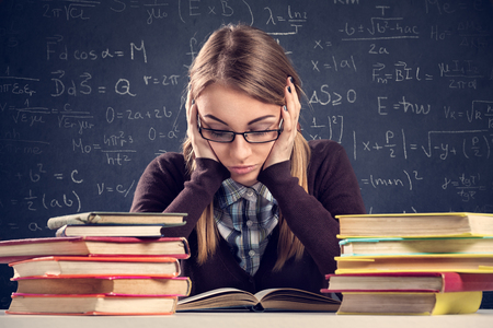 Foto de Young student with desperate expression sitting at a desk and looking at her books - Imagen libre de derechos