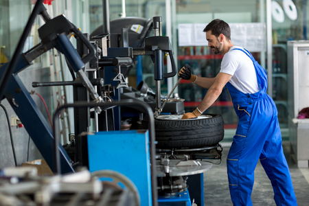 Photo for repairman balancing  car wheel on balancer in workshop - Royalty Free Image