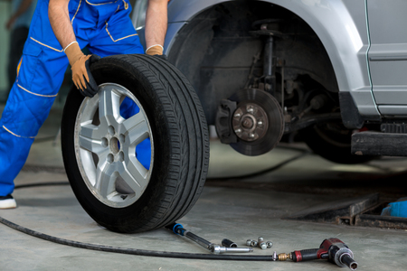 Photo for mechanic changing a wheel of a modern car  in a workshop - Royalty Free Image