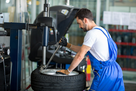 Photo for mechanic replace tires on wheels in a workshop - Royalty Free Image