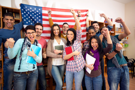 Photo pour Smiling  American students presenting their country with flags - image libre de droit