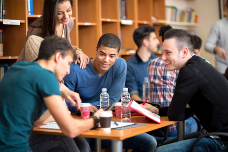 Photo for Few friends socializing and studying together for exam in library - Royalty Free Image