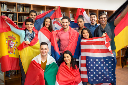 Foto de International multiethnic exchange of students, happy students presenting their countries with flags - Imagen libre de derechos