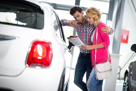 Photo pour Happy couple chooses to buy a car in showroom - image libre de droit