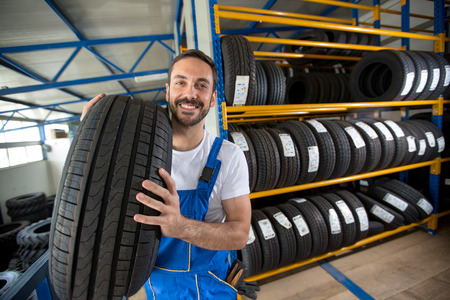 Foto de smiling auto mechanic carrying tire in tire store - Imagen libre de derechos