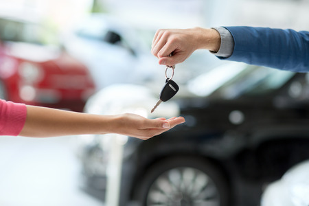 Photo pour Close up of car dealer giving keys to woman - image libre de droit