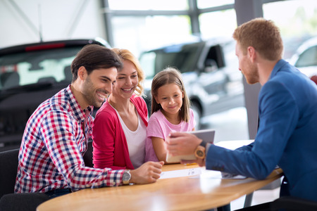 Photo for Young family  in car dealership looking in pc tablet - Royalty Free Image