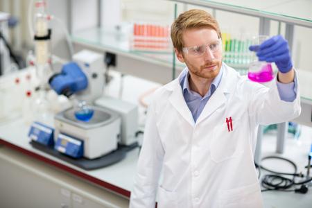 Foto de Young scientist observing liquid reagent in laboratory - Imagen libre de derechos